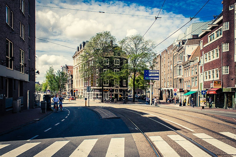 Amsterdam cityscape in color and two bicyclists enjoying their image 1
