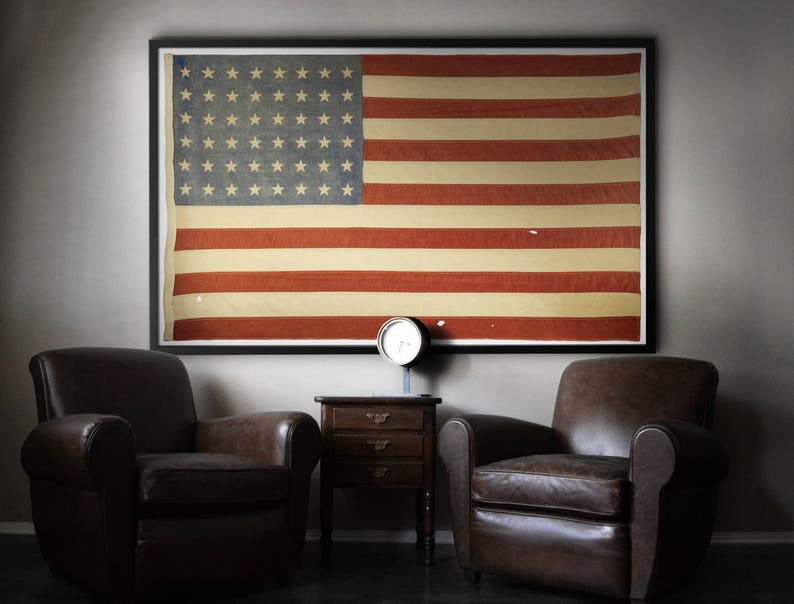 Framed print of vintage American flag on wall with leather club chairs. Come be inspired by 4th of July Tablescapes, Patriotic Decor & USA Finds: Happy Birthday, America in case you're in the mood for American flag and red, white, and blue festive finds.