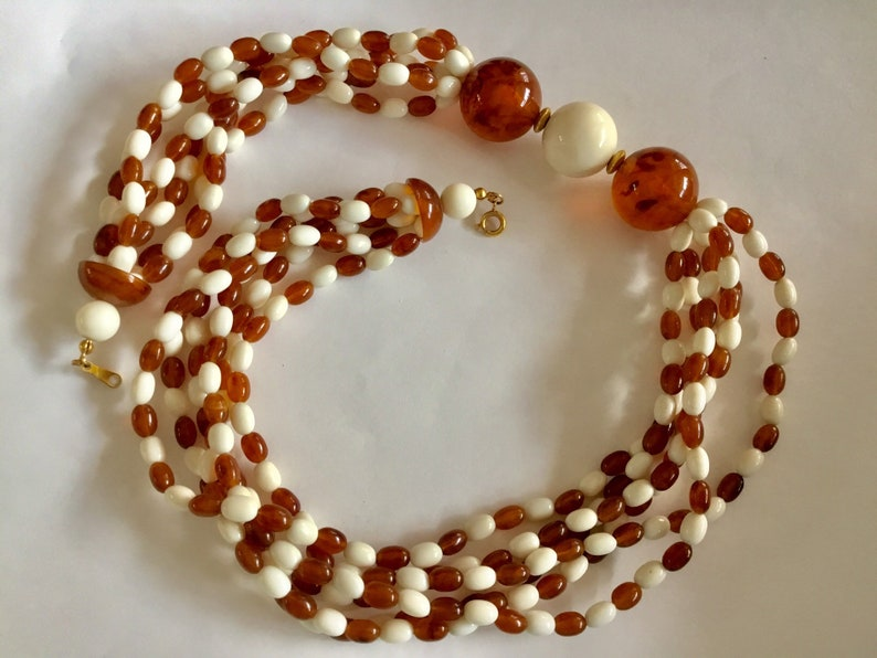 Classic necklace with 6 strands of cream and dark amber glass beads.Lovely mid century necklace with larger beads as focals.