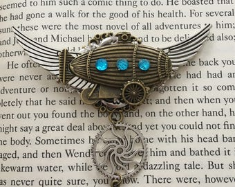 Hand made Steampunk winged brooch badge with bronze airship, blimp, dirigible, zeppelin and multi cogs, gears