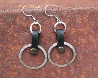Aged silver hoops on a riveted black leather strap earrings.