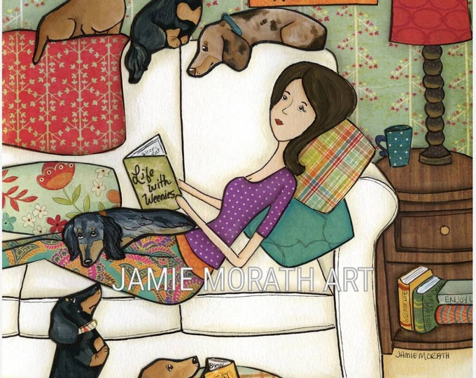 Books and Weenies, dachshund with lady on couch reading book, doxie reading book in dog bed