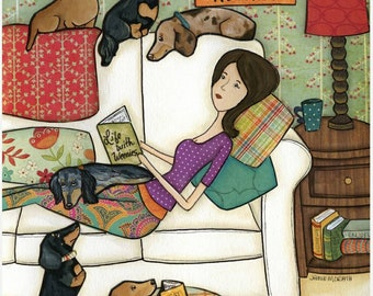 Books and Weenies, lady sitting on couch with dachshund dogs reading a book, doxie laying in dog bed reading book, funny book club humor