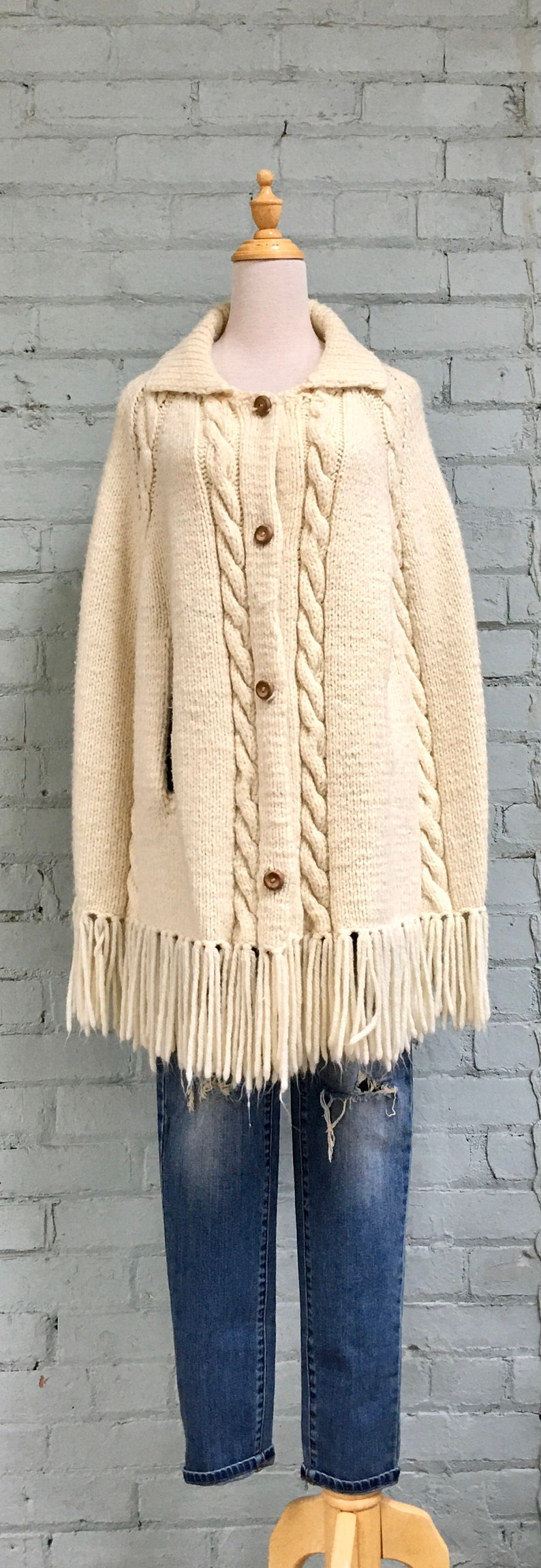 vintage 1970s knit wool poncho  70s fringe button down poncho  cream cable knit cape
