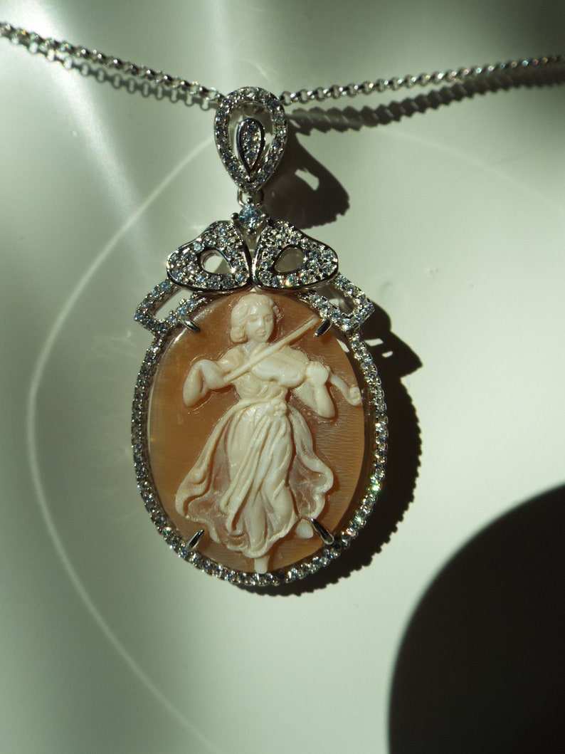 Master hand carved sardonyx cameo set into sterling silver pendant with cubic zirconia