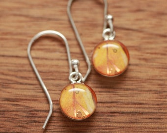 Tiny orange feather earrings made from recycled Starbucks gift cards, sterling silver and resin