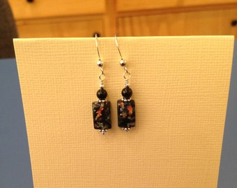 Burst of color radiates from these black glass beads.