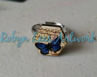 Papillon bleu foncé imprimé hexagone en bois rond avec fond Style parchemin d'écriture sur bague en argent réglable
