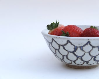 Small handmade ceramic bowl in creamy white with iron-oxide design
