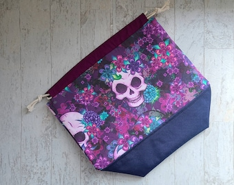 Halloween project bag for knitting, crochet, or embroidery with drawstring and pockets with skulls and flowers print.