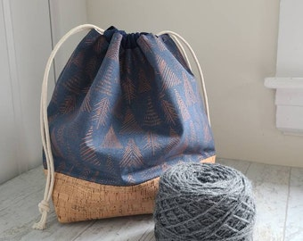 Large project bag for knitting, crochet, or embroidery with drawstring and 2 inner slip pocket; Gold fir trees on blue with cork base
