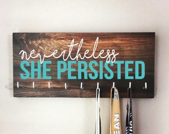 """Race Medal Holder - """"Nevertheless, SHE PERSISTED"""" white and teal with wood grain background - Elizabeth Warren"""