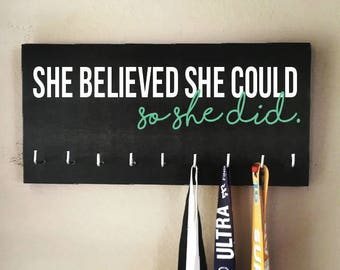 """Race Medal Holder - """"She believed she could SO SHE DID"""" white and teal with black background"""