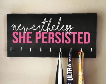 """Race Medal Holder - """"Nevertheless, SHE PERSISTED"""" white and pink with black background - Elizabeth Warren"""