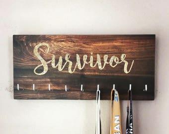 "Race Medal Holder - ""Survivor"" gold glitter with wood grain background"
