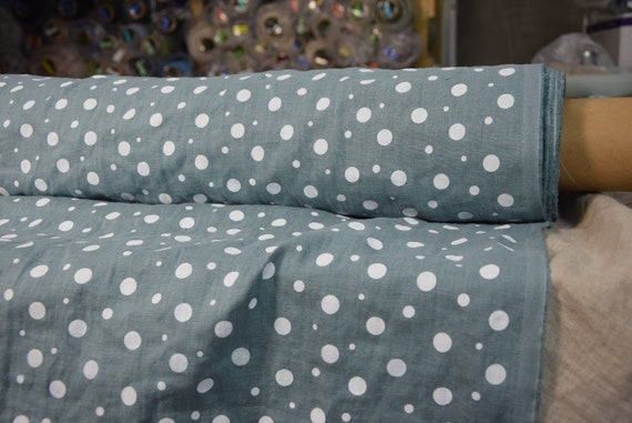 Pure 100% linen fabric Gloria Agave Dotted 190gsm. White pattern dots different sizes on pastel bluish-green background. Washed-softened.
