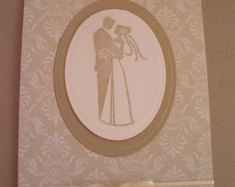 Handmade Wedding card in gold with a stamped image of a bride and groom.