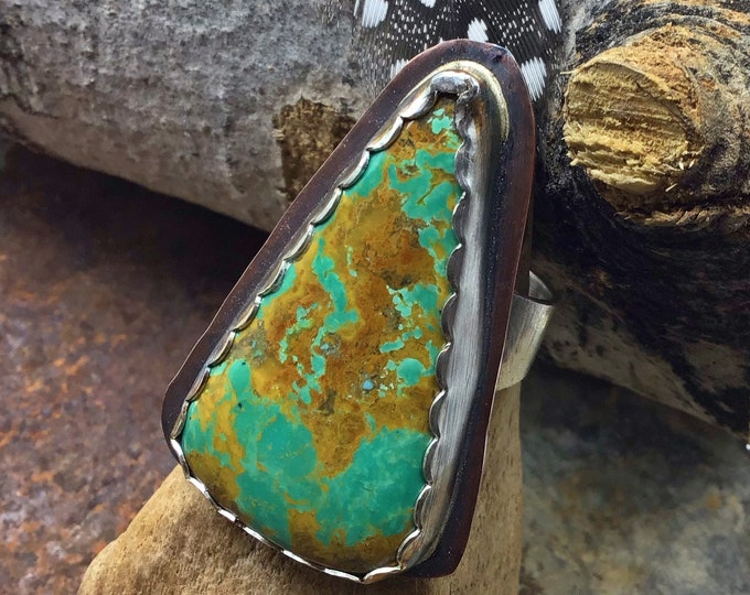 On the long and narrow side turquoise ring with sterling bezel set on copper with sterling wide rustic band, cowgirl