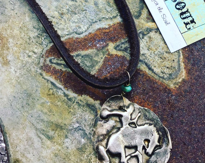 Let r buck bronc in rustic PMC silver on simple thick leather cord set off with a little dot of turquoise, cowgirl style, artisan jewelry,