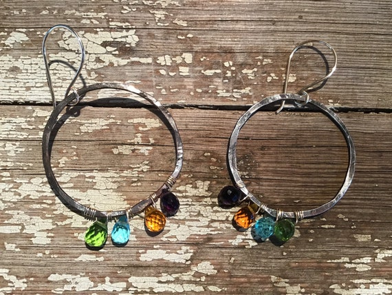 A rainbow of color hoops by Weathered Soul Jewelry, amethyst, peridot, amber, and topaz gems are wrapped at the bottom of these art hoops