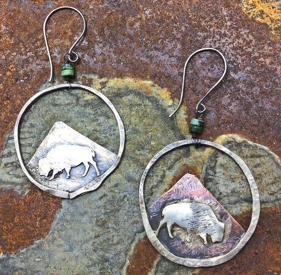 Opposites attract earrings by Weathered Soul jewelry, bison, buffalo, one on sterling, one on copper,mountains behind, turquoise too!