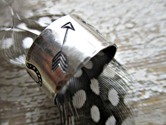 Western lifestyle sterling riveted wide band ring by Weathered Soul, running horse, longhorn, arrows, and horseshoes encompass this ring USA