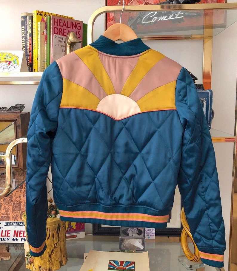 70s Jackets, Furs, Vests, Ponchos Peacock Rising Sun bomber Jacket | Quilted 70s style satin fall Jacket 1970s sunburst teal turquoise blue with mustard coral mauve $149.00 AT vintagedancer.com