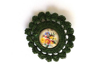 Crocheted brooch in Green with a flower cabochon.