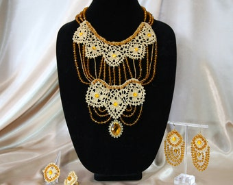 Elaborate beige lace necklace and earrings.