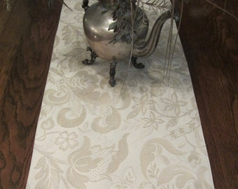 Table runner in white and neutral colored woven botanical fabric, 14 x 86""