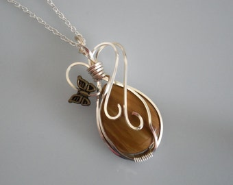 Wire wrapped pendant. Tan bamboo jasper cabochon wrapped with Silver wire. Bronze colored butterfly  embellishment.  Silver chain.