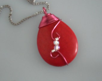 Wire wrapped red stone bead pendant. Wrapped with red copper wire and glass beads
