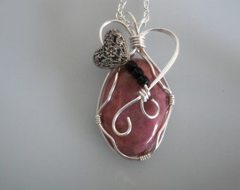 Wire wrapped pendant. Rust red marbled cabochon wrapped with silver plated copper wire. Silver filigree heart & black beads.