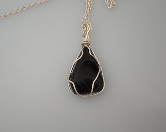 Wire wrapped pendant. Black stone wrapped with silver plated copper wire. Silver chain