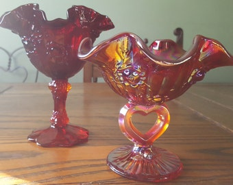 Red glass and amberina glass compotes, likely Fenton, unmarked.
