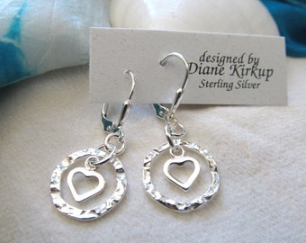 Hammered Sterling Silver Curvy Circles With Small Open Sterling Hearts Nestled In The Circle Presented On Sterling Silver Lever Backs