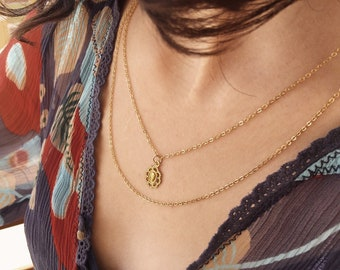 Multi-strand necklace with gilded brass pendants