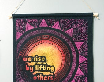 We Rise By Lifting Others Banner. inspirational quotes. positive mantras. lift each other up. block printed banner. sunrise. ALCU Fundraiser