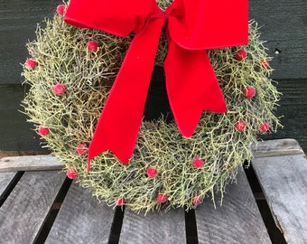 Christmas wreath with red berries snd red ribbon made of natural iron bush and finished with a red velvet bow. Door wreath, red wreath