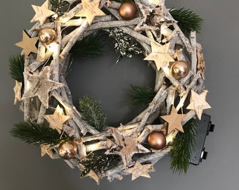 Christmas door wreath with lights, baubles, stars and frosted foilage. Xmas door wreath, christmas decoration.