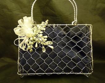 Large bridesmaids metal handbag with a pearl and silver corsage and navy organza background. Pearl brooch bridesmaids handbag, Flowergirl