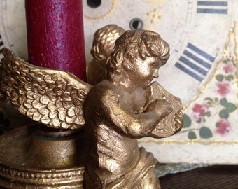 Vintage golden cherub candle holder playing musical instruments.