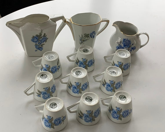White porcelain coffee service with blue roses motif composed of 9 cups and 3 milk and water jugs, art deco, stamped BP France