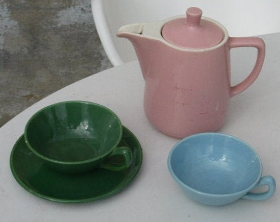 Coffee service consisting of a pink melitta earthenware coffee maker and two earthenware cups, a green and a blue vintage 1950