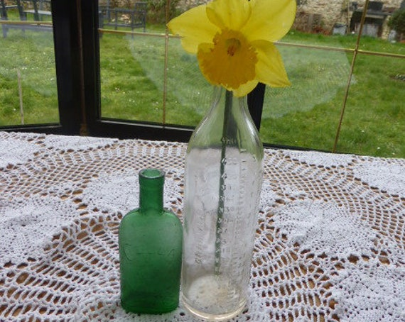 Lot of two bottles, pharmacy bottles, old and collector, green glass ciella and transparent graduated measuring bottles: