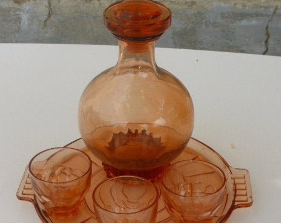 Liquor service in coral pink glass, consisting of a round tray, a bottle decanter and three small vintage glasses 1940