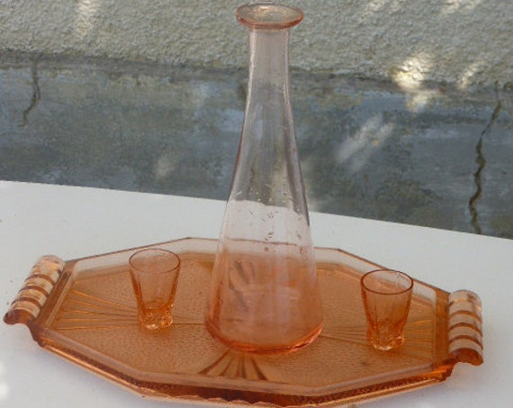 Liquor service in pink glass, consisting of a tray, a bottle decanter and two small vintage glasses 1940