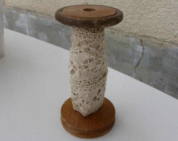 Spool of spinning in wood and metal dressed in old art deco lace