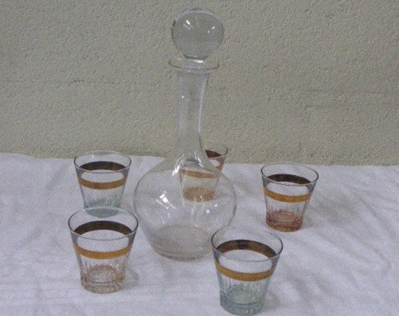 Service consisting of a glass carafe and 5 glasses vintage aperitif 1950, gold edging and each background has a different color