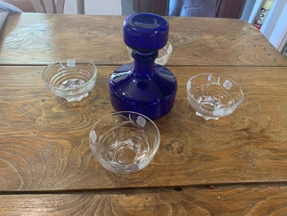 4 champagne glasses with flowers and a small carafe, blue glass bottle